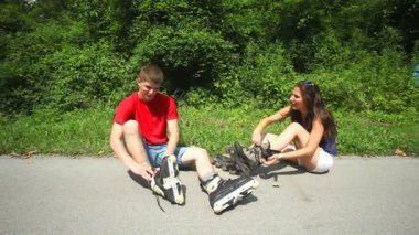 Young woman and man sitting on track, putting their rollerblades on their feet. — Stok video