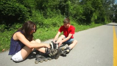 Young woman and man sitting on track, putting their rollerblades on their feet. — Stock Video