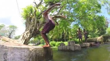 Young boy doing a backward somersault into river. — Stock Video