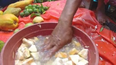 Hand washing sliced jack fruit slices in water bowl. — Stock Video