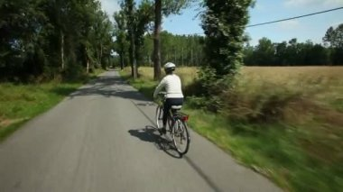 Woman cycling on road in countryside — Stock Video