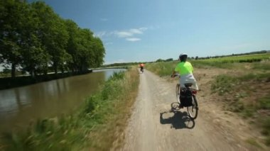 Retired couple cycling beside river — Stok video