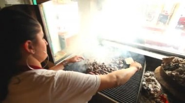 Woman grilling cevapi on grill in restaurant — Wideo stockowe