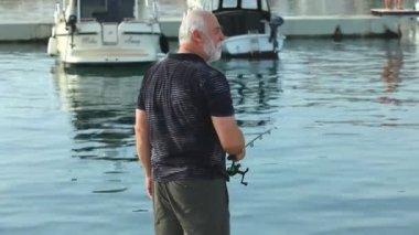 Fisherman in old town Krk harbour — Stock Video