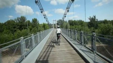 Woman cycling on road over bridge — Stock Video