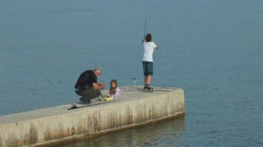 Family fishing in old town Krk harbour — Stock Video