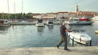 Fisherman in old town Krk harbour — Stock Video