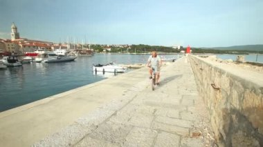 Man cycling in harbour of old town Krk — Stock Video