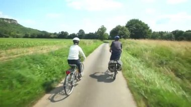 Retired couple cycling on road — Stock Video