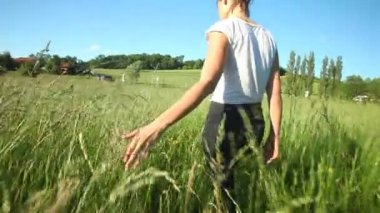 Woman walking touching long grass — ストックビデオ