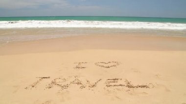 Ocean wave covering words I love travel written in sand on beach — Video Stock