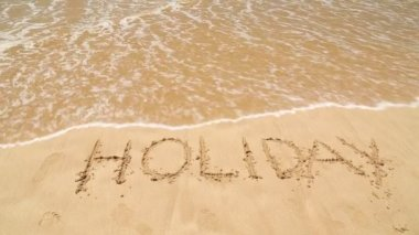 Ocean wave covering word holiday written in sand on beach — Stock Video