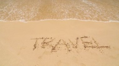 Ocean wave covering word travel written in sand on beach — Stockvideo