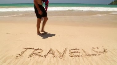 Young man walking in front of word travel written in sand on beach — Wideo stockowe