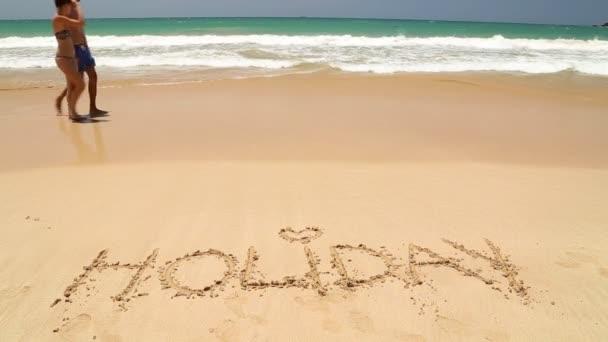 Gente caminando por delante de vacaciones de la palabra escrita en la arena — Vídeo de stock