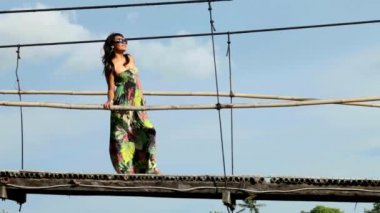 Woman standing on suspension bridge — Vídeo Stock