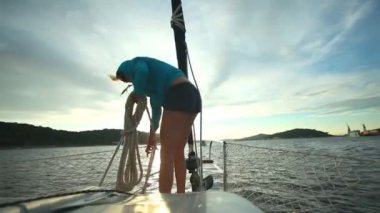 Woman preparing ropes on bow of sailboat — Stok video
