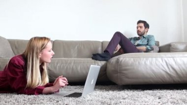 Woman on carpet looking at laptop with man on couch — Stockvideo