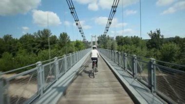 Woman cycling on road over suspension bridge — Video Stock