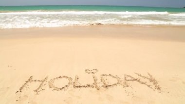 Ocean wave covering word holiday — Wideo stockowe