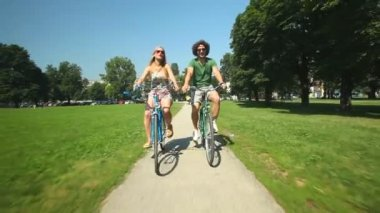 Couple enjoying cycling through park — Vídeo de stock