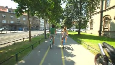 Couple enjoying cycling through park — Stockvideo