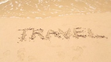 TRAVEL written on beach sand — ストックビデオ