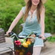 Attractive blonde woman with straw hat riding a bike with basket full of groceries. — Stock Photo #70347101
