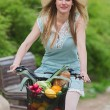 Attractive blonde woman with straw hat riding a bike with basket full of groceries. — Stock Photo #70347105