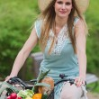 Attractive blonde woman with straw hat riding a bike with basket full of groceries. — Stock Photo #70347115