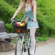Attractive blonde woman with straw hat riding a bike with basket full of groceries. — Stock Photo #70347125