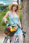 Attractive blonde girl with straw hat standing in the park and posing next to bike with basket full of groceries. — Stock Photo