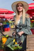 Attractive blonde woman with straw hat and bike on Marketplace. — Stock Photo