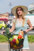 Attractive blonde woman with straw hat posing next to bike with basket full of groceries. — Stock Photo