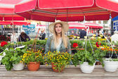 Attractive blonde woman with straw hat posing on flower marketplace. — Stock Photo