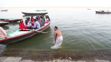 Boat arriving to the shore of Ganges, while man baths aside. — Stock Video