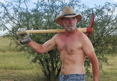 A Shirtless Cowboy Shoulders a Red Pickax — Stock Photo