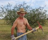 A Shirtless Cowboy Uses a Red Pickax — Stock Photo
