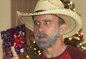 A Bearded Cowboy Tries to Guess His Christmas Present — Stock Photo