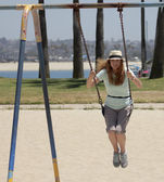 A Woman Swings in a Park by a Bay — Stock Photo
