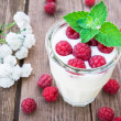 Glass of yogurt with raspberry — Stock Photo #53037681