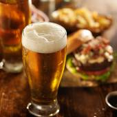 Cold beer with foamy head and burgers — Stock Photo