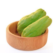 Chayote squash, also known as choko in wooden bowl on white — Stock Photo