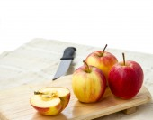 Small gala apple on wooden chopping board over white.  — Stock Photo