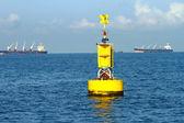 Floating yellow navigational buoy on blue sea — Stock Photo