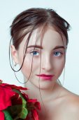 Beauty portrait of young girl. Morning image with the effect of wet face. The girl in the hands holding a red flower. — Stockfoto