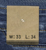 Tag on jeans background — Stock Photo