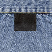 Black tag and  blue jeans texture — Stock Photo