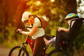 Young woman on a bicycle with little daughter  behind — Stock Photo