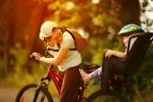 若い女性の後ろに小さな娘と自転車に乗って — ストック写真